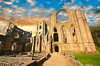 Exterior at sunrise  of the ruins of Fountains Abbey , founded in 1132, is one of the largest and best preserved ruined Cistercian monasteries in England. The ruined monastery is a focal point of England's most important 18th century Water, the Studley Royal Water Garden which is a UNESCO World Heritage Site. Near Ripon, North Yorkshire, England