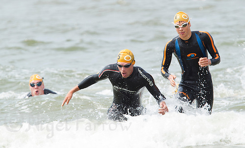 13 JUL 2013 - DEN HAAG, NED - Pavel Andreev (RUS) (centre) of Russia runs through the surf at the end of the swim during the 2013 ITU Cross Triathlon World Championships  in Kijkduin, Den Haag (The Hague), the Netherlands (PHOTO COPYRIGHT © 2013 NIGEL FARROW, ALL RIGHTS RESERVED)
