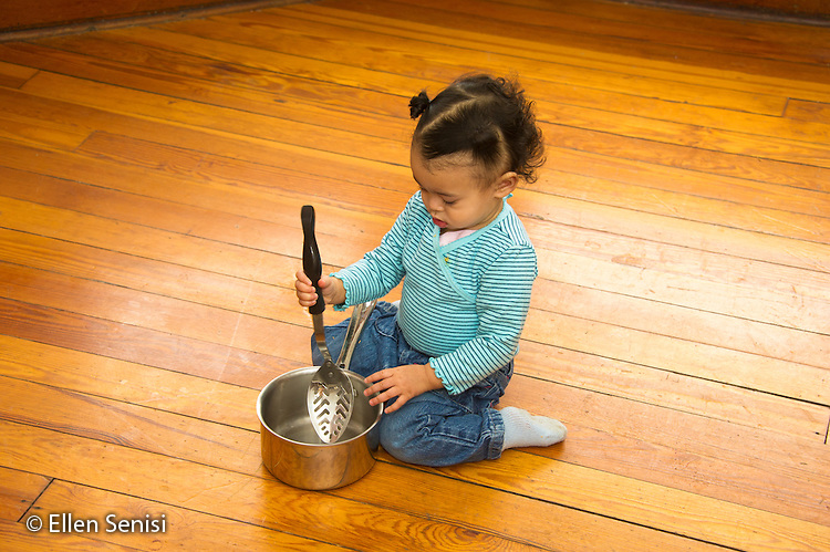 MR / Schenectady, NY. Toddler (1 African-American and Caucasian) uses a pot and spoons as toys to play. MR: Dal4. ID: AM-HD. © Ellen B. Senisi