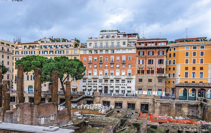Travel Art Landscape Print Photograph. <br /> The Largo di Torre Argentina is a square in Rome, Italy, that hosts four Republican Roman temples, and the remains of Pompey's Theatre. It is located in the ancient Campus Martius.<br /> The ancient Roman ruins within this photograph are beautifully surrounded by the colourful backdrop of the city's buildings, the trees, and the dramatic cloud formations that are seen above the buildings. All of these elements work together to enhance the emotion of this scene.