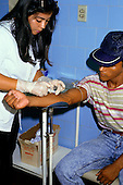 Manaus, Brazil. Health worker wearing rubber gloves taking a blood sample at a leprosy (Hansen's disease) clinic.