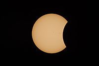 The Moon begins to cover the Sun's disk in the partial eclipse phase after first contact during the Great American Eclipse on August 21, 2017.  Sunspots are visible on the sun's surface.