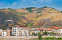 The town Tain l'Hermitage, the riverside side, the river Rhone.  The name of the town painted in large white lettres   The Hermitage vineyards on the hill behind the city Tain-l'Hermitage, on the steep sloping hill, stone terraced. Sometimes spelled Ermitage.  Tain l'Hermitage, Drome, Drôme, France, Europe