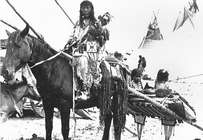 1900 historic photograph by .Franklin Johnson of a Blackfeet family being transported on a horse travois