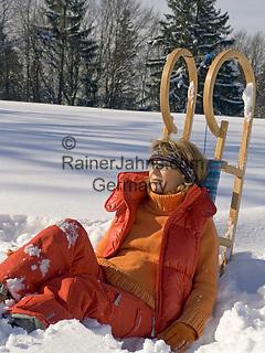 Deutschland, Frau mit Schlitten sitzt im Schnee   Germany, woman with sledge sitting in the snow