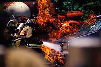 Firemen putting out a car fire.