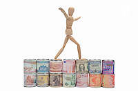 Wooden mannequin balancing on a line of tin cans surrounded by worldwide international banknotes like the Us Dollars, the Euro and the chinese Yuan, symbolizing the international finance and the currencies exchange rate competition, studio shot on white background  (Licence this image exclusively with Getty: http://www.gettyimages.com/detail/102918632 )