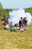 Cannon fires as cannoneer of Continental Artillery unit touches the linstock, holding a slow burning match at the end, to the priming powder in the vent hole, at a Revolutionary War encampment on Bemis Heights, site of a major British defeat in October 1777, Saratoga National Historical Park, Stillwater, New York, USA.