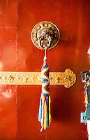 Kathmandu Nepal Door handle with colorful welcome thong hanging at the Drikung Kagyu Rinchenling monastery Eastern Kathmandu.