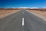 Marokko, Region Souss-Massa-Draâ, bei Tinghir (Tinerhir): Landstrasse durch die Wueste im Sueden des Landes, im Hintergrund die schneebedeckten Berge des Hohen Atlas Gebirges | Morocco, Region Souss-Massa-Draâ, near Tinghir High Atlas: Desert road