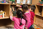 Preschool 4-5 year olds two girls and a boy playing with toy dinosaurs in block area seen from the back