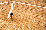 """Workers sweep rice into mesmerising parallell lines to dry in the midday sun in Ashoknagor, India.<br /> <br /> The images were captured by Avishek Das, 35, from Kolkata, India.<br /> <br /> Avishek said, """"The drying of the paddy grains is one of the most important steps in the process before they are sent to the rice mill.""""<br /> <br /> """"Drying reduces the moisture in the grains to a level which makes them suitable for storage.  The workers start very early in the morning, between 3 and 4am, but earn very little - only £2.50 per day.""""<br /> <br /> """"I like photographs with lines and patterns, and there is a strong sense of perspective created in these images.""""<br /> <br /> Please byline: Avishek Das/Solent News<br /> <br /> © Avishek Das/Solent News & Photo Agency<br /> UK +44 (0) 2380 458800"""