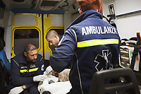 Switzerland. Canton Ticino. Lugano. A man lying down on an emergency medical stretcher is brought at night time by ambulance to hospital for medical examination. The man is suffering from with drug abuse. Team paramedics wear blue uniforms and medical gloves. They all work for theCroce Verde Lugano. The man (L) and the woman (R) are professional certified nurses, the bald man (C) is a volunteer specifically trained in emergency rescue. The patient is connected to a monitor which controls a set of vital functions, such as  electrocardiogram, blood pressure's measurement, respiratory rate and pulse oximetry (oxygen saturation). TheCroce Verde Lugano is a private organization which ensure health safety by addressing different emergencies services and rescue services. Volunteering is generally considered an altruistic activity where an individual provides services for no financial or social gain to benefit another person, group or organization. Volunteering is also renowned for skill development and is often intended to promote goodness or to improve human quality of life. Switzerland. Canton Ticino. Lugano. A paramedic takes care of an injured child lying down on stretcher during an emergency medical ride by ambulance. The baby boy fell at home, hurt his head and is brought to hospital for a medical examination. The  paramedic is a professional certified nurse, wearing a blue uniform medical gloves. He works for theCroce Verde Lugano. The bearded paramedic smiles, talks to the child and shows him a brown stuffed bear. TheCroce Verde Lugano is a private organization which ensure health safety by addressing different emergencies services and rescue services. Medical gloves are made of different polymers including latex, nitrile rubber, polyvinyl chloride and neoprene. 20.01.2018 © 2018 Didier Ruef