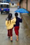 Two young Guatemalan girls walking in rain under umbrella, Nebaj, western highlands, Guatemala