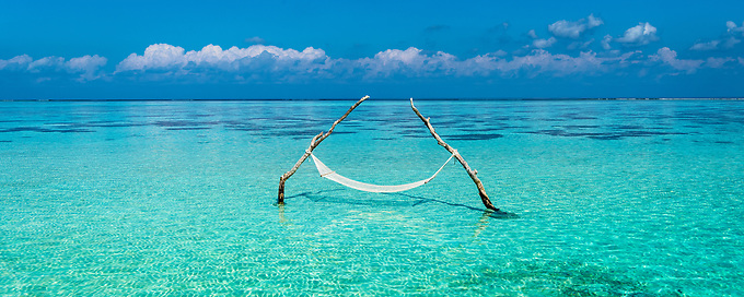 This panoramic view shows the expanse of the aquamarine water of the Indian Ocean surrounding a hammock in a shallow lagoon.
