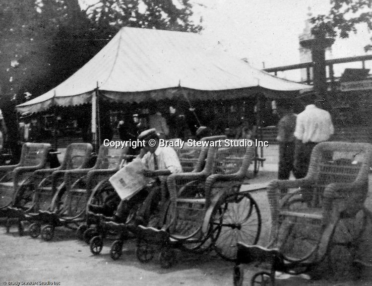 Client: St Louis World's Fair<br /> Product: Transport Wheel Chairs<br /> <br /> St Louis MO:  View of the carriage station at the Louisiana Purchase Exposition. Operator reading the paper while waiting for customers.
