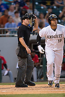 Home plate umpire Matt McCoy watches the flight of the ball as Matt Tuiasosopo (18) starts down the first base line during the game against the \in at BB&T BallPark on June 20, 2015 in Charlotte, North Carolina.  The Knights defeated the Indians 6-5 in 12 innings.  (Brian Westerholt/Four Seam Images)