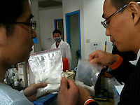 Eric Chang (R), 35, owner of CEC Limited, a company which exports MDPV, a legal high, to Great Britain, is seen checking bags of an unidentified 'new product' with a member of his staff, (L), in his laboratory in Pudong, Shanghai, China, 08 April 2010.
