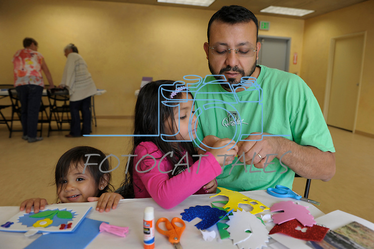 Avani Martinez, 4, center, and her dad Gilbert work on a craft project as little sister Adi, 1, peaks over the table during Nevada Wildflower Family Fun Day at the Nevada State Museum in Carson City Saturday April 11, 2015. The Sparks family  was treated to information, hands-on experiences and crafts.<br /> Photo by Lisa J. Tolda