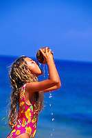 Girl drinking from coconut. Ulua Beach, Wailea, Maui
