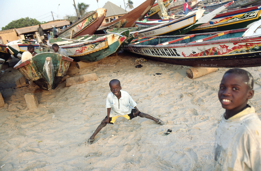 Senegal. Dakar. Sombedioune district (neighborhood).                                                          Every day, a fish market takes place on the beach where the fishermen are returning with their boats and with new fresh fishes. Children play on the sand close to the boats. Atlantic ocean.© 2000 Didier Ruef