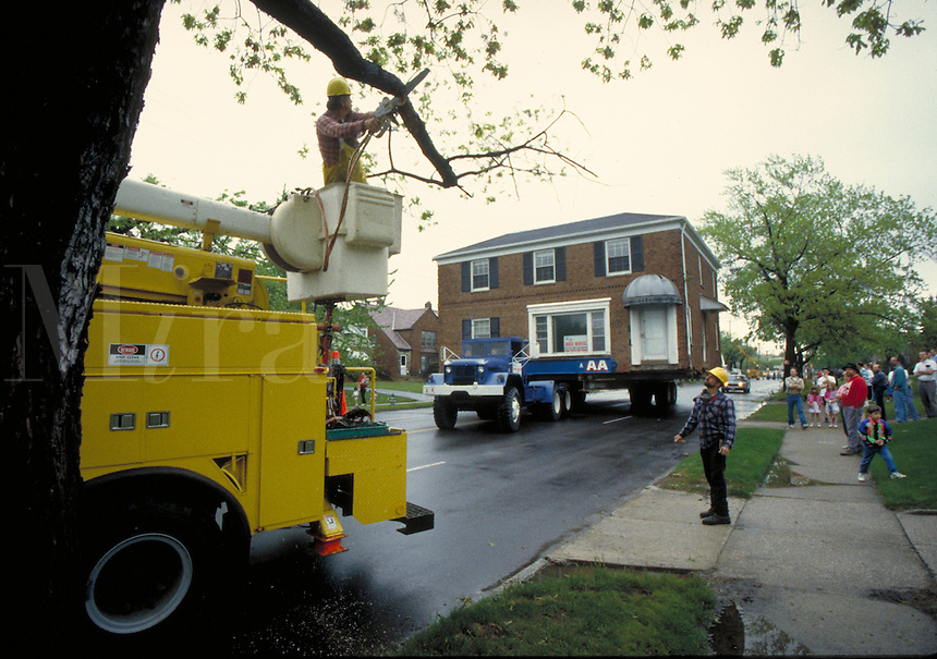 Worker remove tree limb to make room for house being moved via truck.