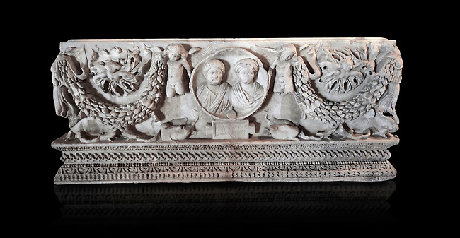 Roman sarcophagus with relief sculptures from Hierapolis . Hierapolis Archaeology Museum, Turkey.<br /> <br /> Sarcophagus With Garland.<br /> <br /> They were widely used in the valley of Menderes from the beginning of the 2nd century A.D. The Nike on the edges and the Eros in the middle of the long sides carry the garlands. There are Medusa masks on the upper spaces of the garlands, sometimes the portraits of the owners of the tombs and some mythological descriptions take place here. Medusa masks symbolise the protection of the tomb where as the garlands symbolise the meeting of the owner in the other world. Ostoteks are also made in the some manner.  . Against an black background