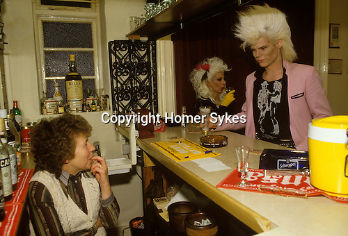 Newcastle upon Tyne, Tyne and Wear. 1986<br /> Sigue Sigue Sputnik band members Neal Whitmore aka Neal X and Jane Farrimond known as Yana Yaya at the bar of a Cherton Hotel. Neal is wearing a Cowboy  t-shirt based on a design by gay artist Jim French.  The landlady looking  surprised serves the drinks before that evenings Love Missile F1-11 gig at Tiffany's in Newbridge Street.<br /> Bed and Breakfast Hotel landlady. Cherton Hotel, Clifton Road, Newcastle upon Tyne, UK. March 12th 1986. <br /> Jim French (14 July 1932 - 16 June 2017) American photographer and illustrator.