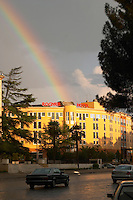 The Rogner Hotel in sunshine with a rainbow in the sky. On the Boulevard Bulevardi Deshmoret e Kombit. Tirana capital. Albania, Balkan, Europe.