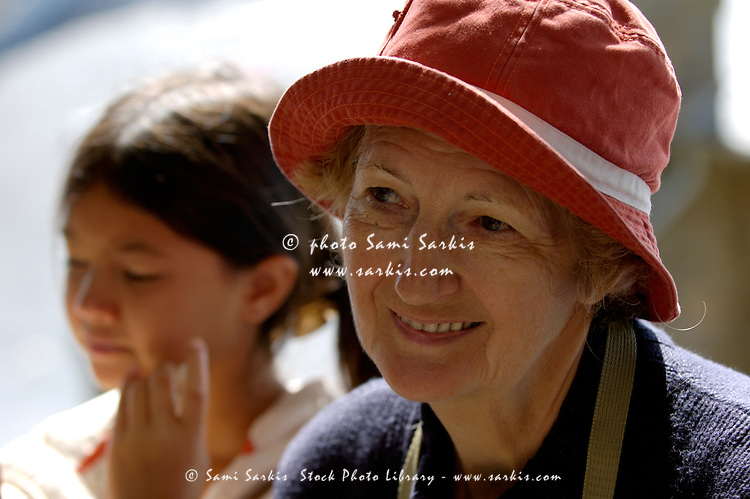 Portrait of a senior woman wearing a sun hat with her granddaughter in the background.