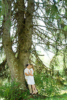 Couple in embrace leaning against tree<br />