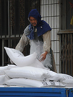 "a man unloads chemicals at Xiditou. Xiditou is known as one of China's worse ""cancer villages"" where a reported ten percent have died from cancer."