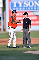 Greensboro Grasshoppers manager Todd Pratt (55) discusses call with umpire Sam Burch during a game against the  Asheville Tourists at McCormick Field on April 28, 2017 in Asheville, North Carolina. The Grasshoppers defeated the Tourists 7-4. (Tony Farlow/Four Seam Images)
