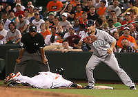 Casey Kotchman #13 of the Seattle Mariners fails to tag Brian Roberts #1 of the Baltimore Orioles at first during a MLB game at Camden Yards, on August 8 2010, in Baltimore, Maryland. Orioles won 5-4 in extra innings.