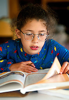 Portrait of a young girl wearing glasses as she reads while doing her homework.