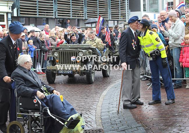 Wageningen, 050512<br /> Bevrijdingsdag, een veteraan geeft onder luid applaus van het publiek een agent drie zoenen op haar wang.<br /> Foto Alice van Schuppen - APA Foto