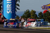 The #10 SunTrust Racing Pontiac/Riley of Max Angelelli leads the #01 Chip Ganassi Racing with Felix Sabates Lexus/Riley of Scott Pruett in the closing laps.