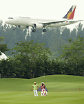 SINGAPORE - MARCH 07:  Eun-Hee Ji of South Korea waits with her caddie on the par five 15th hole as a plane flys overhead during the third round of HSBC Women's Champions at the Tanah Merah Country Club on March 7, 2009 in Singapore. Photo by Victor Fraile / The Power of Sport Images