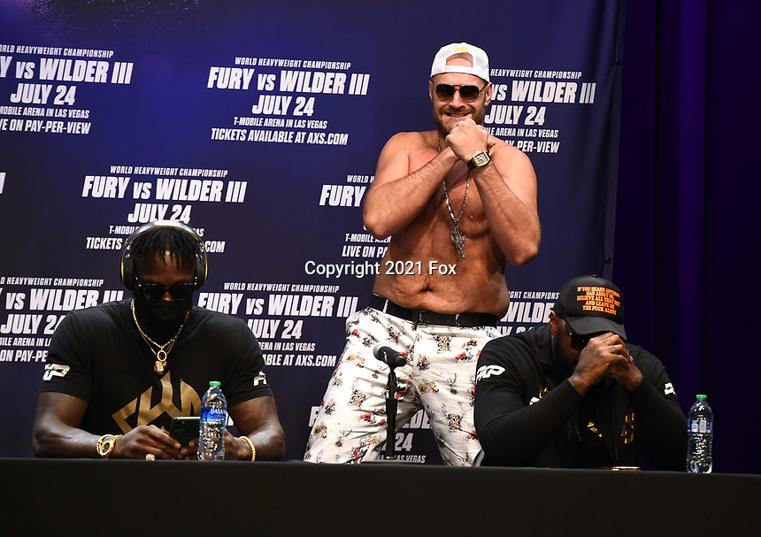 """LOS ANGELES, CA - JUNE 15: Boxers Tyson Fury stands behind Deontay Wilder and trainer Malik Scott at a press conference for the FOX Sports PPV """"Tyson Fury vs. Deontay Wilder III"""" at The Novo by Microsoft at LA Live on June 15, 2021 in Los Angeles, California. Fury vs. Wilder will be on July 24 at the T-Mobile Arena in Las Vegas. (Photo by Frank Micelotta/HULU/PictureGroup)"""