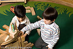 Education Preschool 3-5 year olds block play two boys building together plastic toy animals on construction horizontal