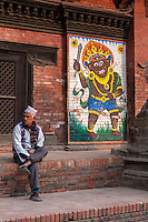 Nepal, Patan, Durbar Square.  Man Sitting next to a Painting of Bhairab (Bhairav), a Fierce Manifestation of the Lord Shiva.