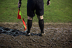 Belper Town 4 Gresley 1, 28/01/2014. Christchurch Meadow, Northern Premier League. The referee's assistant standing in the mud during the second-half of Belper Town's match against Gresley, in a Northern Premier League, first division south fixture at Christchurch meadow. The home side have played at their current ground since the club was reformed in 1951. Belper won this fixture against their local Derbyshire rivals by 4 goals to 1 watched by a crowd of 165 spectators. Photo by Colin McPherson