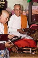 Myanmar, Burma.  Mandalay.  Two Buddhist Nuns and Friend Examining Sandals.  Buddhist nuns shave their heads, as do men.