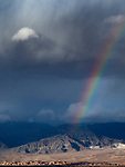 Rainbow appears over the Grapevine Mountains and Mesquite Flats Sand Dunes during a passing winter storm in Death Valley National Park, California