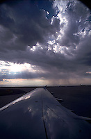 View out of airplane window; airplane wing and storm clouds<br />