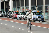 A man wearing a helmet cycles past a taxi rank outside St.Pancras International station, London.