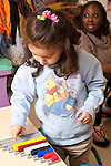 Education preschool girl counting cubes she has placed in staggered rows in plastic tray