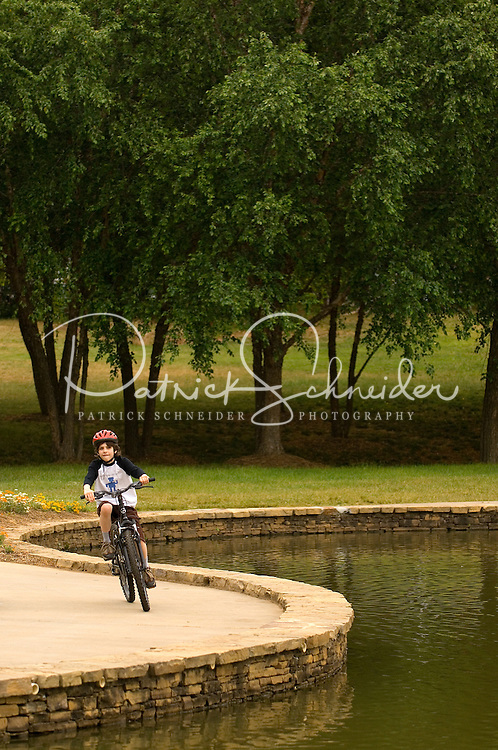 A boy rides his bike past the lake at Freedom Park in the Myers Park neighborhood in Charlotte, NC. Myers Park is one of the premier neighborhoods in North America and known for its large canopy of trees.