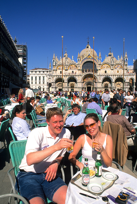 Tourist couple having drink at cafe in front of the Famous St Marks Church in San Marcos Plaza in romantic Venice Ital