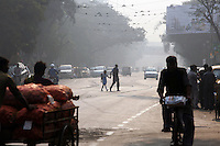 """Against smoggy skies, a man walks his daughter across a busy street in central Kolkata. According to the Delhi-based Center for Science and Environment, """"18 out of every 100,000 persons in Kolkata fall victim to lung cancer annually. Seven out of 10 people in Kolkata are afflicted with some form of respiratory ailment. Also the percentage of children suffering from upper respiratory infections, cough, wheezing and eye irritation is increasing in direct proportion to the increasing concentration of PM10 [particle pollution].""""  India. November, 2013"""